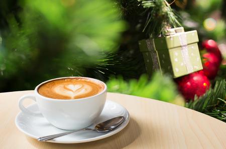美しいクリスマス光祭り、白いコーヒー カップ ボケ背景に木製のテーブルの上の写真。