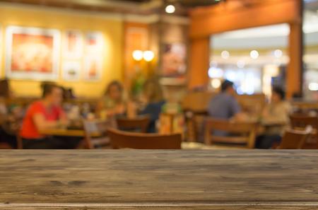 選択したフォーカス空茶色の木製のテーブルとコーヒー ショップは、ピンぼけ画像で背景をぼかし。あなたのフォト モンタージュや製品表示。 写真素材