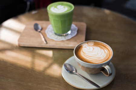 Hot drinks with latte coffee matcha green tea on wooden table.