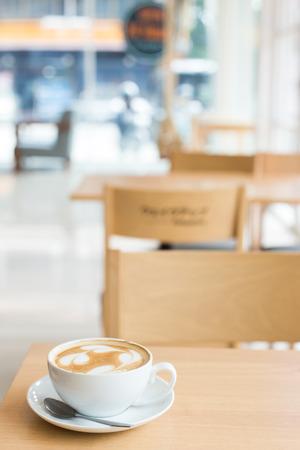木製のテーブルの上にカップのラテ コーヒー アート。