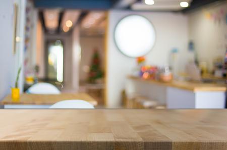 Enfoque seleccionado vacío marrón mesa y café de madera tienda de desenfoque de fondo bokeh con. para su fotomontaje o exposición del producto.