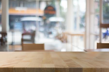 La mesa de madera marrón vacía del foco seleccionado y la cafetería empañan el fondo con imagen del bokeh. para su fotomontaje o exhibición del producto.