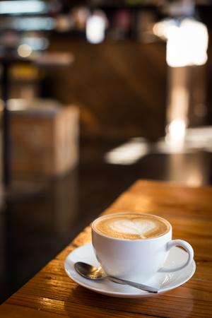 木製のテーブルの上にカップのラテ コーヒー アート