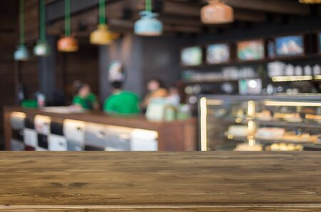 customer focus: Selected focus empty brown wooden table and Coffee shop blur background with bokeh image. for your photomontage or product display