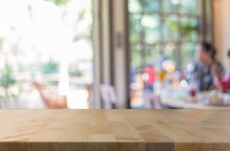 customer focus: Selected focus empty brown wooden table and Coffee shop blur background with bokeh image, for product display montage.