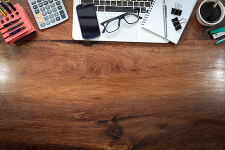 Laptop on Vintage Wooden desktop in modern office with accessories - top view on desk from above. Stock Photo