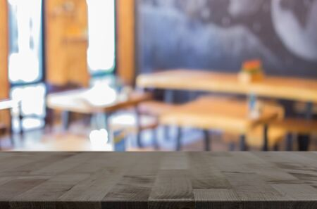 restaurant dining: Selected focus empty brown wooden table and Coffee shop blur background with bokeh image, for product display montage.
