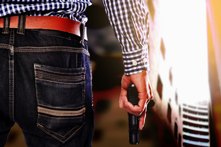 concealed: Back view of man in black glove with a gun in hand, retro effect. Stock Photo
