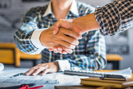 builders: architecture and home renovation concept - builder with blueprint shaking partner hand in retro style.