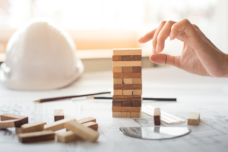 Planning, risk and strategy in business, businessman and engineer gambling placing wooden block on a tower