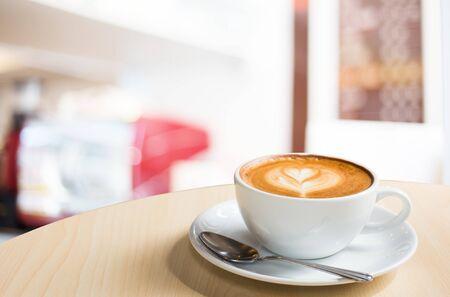 Il caffè caldo del latte di arte in una tazza sulla tavola di legno e la caffetteria sfocano il fondo con l'immagine del bokeh