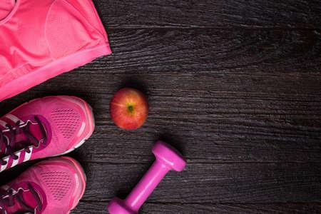 deporte: El deporte femenino sujetador, artículos de pie, Pesa y manzana en el fondo de madera oscura. el desgaste físico y equipo. Moda deportiva, accesorios deportivos, equipo deportivo. para el concepto de salud