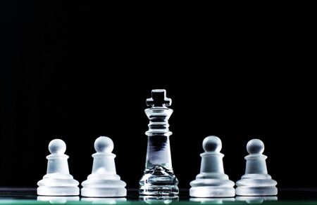 inequality: King and several pawns on chessboard in dark background. Hierarchy concept.
