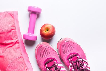 女性のスポーツのブラ、足ウェア、ダンベルとアップル。フィットネスウェアと機器。スポーツ ファッション、スポーツ アクセサリー、スポーツ装