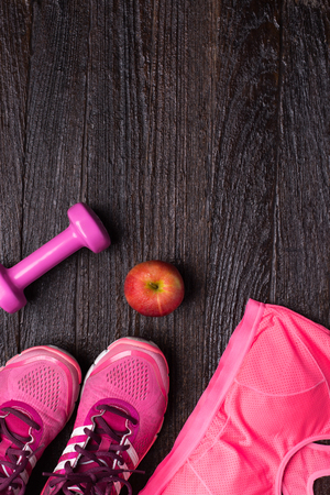 foot ware: Womens sports bra,foot ware, Dumbbell and apple on dark wooden background. Fitness wear and equipment. Sport fashion, Sport accessories, Sport equipment. for healthy concept. Stock Photo