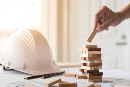 tower block: Planning, risk and strategy in business, businessman and engineer gambling placing wooden block on a tower