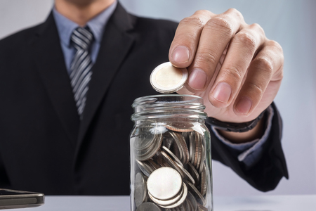 clear bottle: Hand putting mix coins and seed in clear bottle and copyspace, Business investment growth concept. Stock Photo