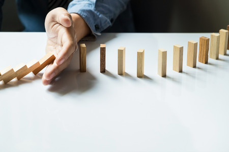 toppled: businessman hand stop dominoes continuous toppled or risk with copyspace