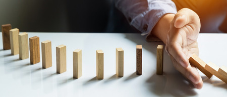 topple: businessman hand stop dominoes continuous toppled, Panoramic composition suitable for banners