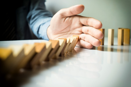 chain reaction: businessman hand stop dominoes continuous toppled or risk with copyspace
