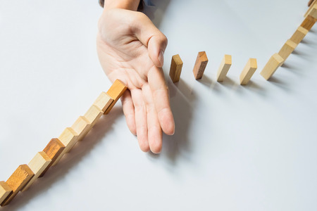 obstruction: businessman hand stop dominoes continuous toppled or risk with copyspace