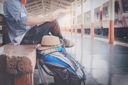 travel: 一名年輕男子坐在旅行者地圖的側面肖像選擇在哪裡旅行,包等待火車,復古色調濾鏡影響