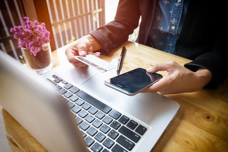 inputting: Cropped image of woman inputting card information and key on phone or laptop while shopping online. Stock Photo