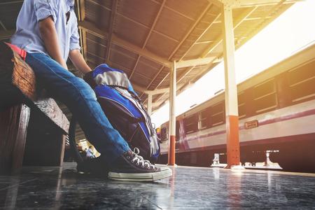 待っている若い男が旅行者の肖像画は、鉄道、旅行バッグ。