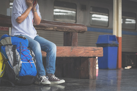 chilled out: Portrait of a young man traveler waiting for train and travel bag.