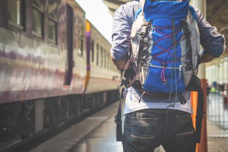 waits: traveler man waits train on railway platform.