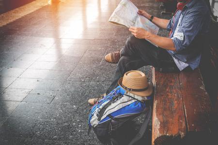 Retrato lateral de un viajero joven sentado con el mapa de elegir dónde viajar y la bolsa esperando el tren, filtro de tono de época efectuado