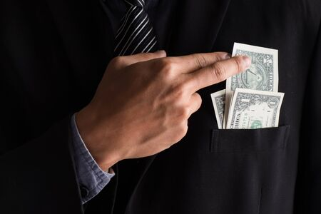 hand in pocket: Business hand is putting money in the pocket. Stock Photo
