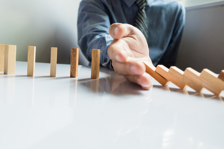 intervene: businessman hand stop dominoes continuous toppled or risk with copyspace