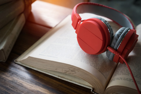 Concept of audiobook. Books on the table with headphones put on them.
