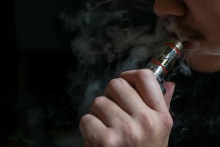 物議を醸す vaping 電子タバコを喫煙隠されたアイデンティティを持つ男。Vaping 健康コミュニティが安全な場合や健康上のリスクの議論の余地は 写真素材