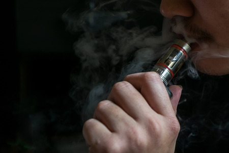 concealed: Man with concealed identity smoking a controversial vaping an electronic cigarette. Vaping is debatable in the health community if it is safe or a health risk Stock Photo