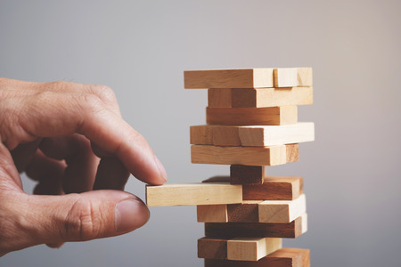 tower block: Planning, risk and strategy in business, businessman and engineer gambling placing wooden block on a tower.