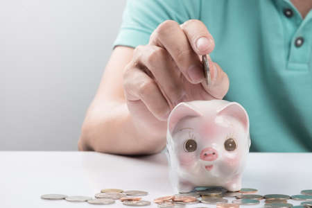 depositing: Young businessman depositing money in piggy bank.