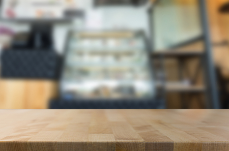 customer focus: Selected focus empty brown wooden table and Coffee shop blur background with bokeh image, for product display montage Stock Photo