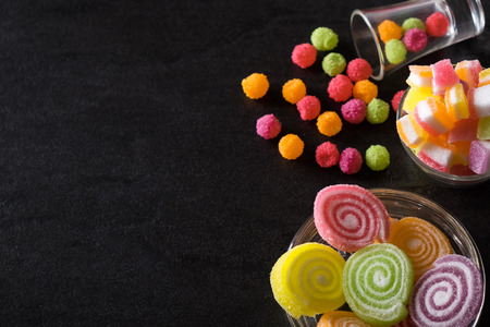 Colorful candies, jelly and marmalade and jellybeans around a central copy space on slate on background. Top view with copy space. Stock Photo