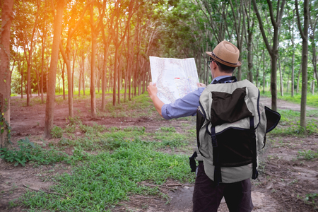 explorer man: portrait of adventure man with map and extreme explorer gear on forest with sunrise or sunset. Stock Photo