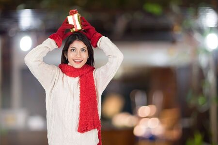 christmas, x-mas, new year, winter, happiness concept - smiling woman in santa helper hat with gift box. Stock Photo