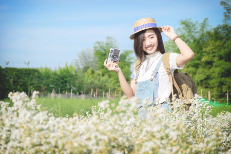 picture framing: Asian hipster cute teen girl with camera in white flower garden, with vintage tone nature concept.