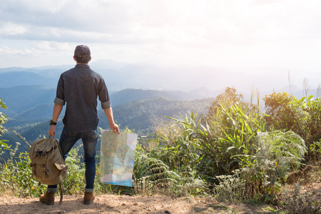 Jonge Man Traveler met kaart rugzak ontspannen buiten met rotsachtige bergen op de achtergrond van de zomer vakanties en Lifestyle wandelen concept.