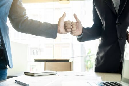 Two young business man a thumb up sign during discussion a meeting. Stock Photo