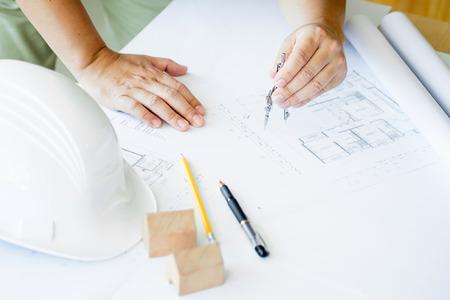 Close-up van de hand Drawing Plan Person's On Blue Print met architect apparatuur