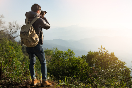 Young professional traveler man with camera shooting outdoor, fantastic mountain landscape Stock Photo