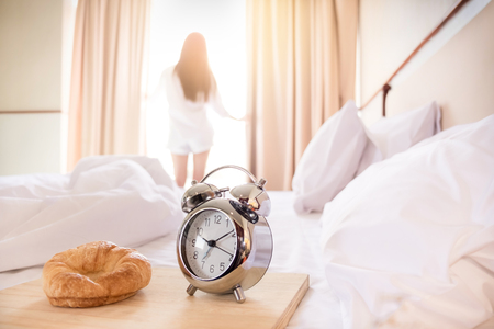 Woman stretched in bed room after the alarm clock and bread in the sunlight morning Imagens - 72811255