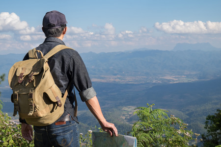 Young Man Traveler with map backpack relaxing outdoor with rocky mountains on background Summer vacations and Lifestyle hiking concept.