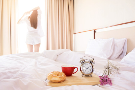 Woman stretched in bed room after the alarm clock and bread in the sunlight morning